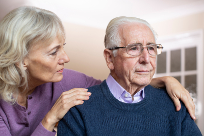 Confused Senior Man Suffering With Dementia Being Comforted By Wife