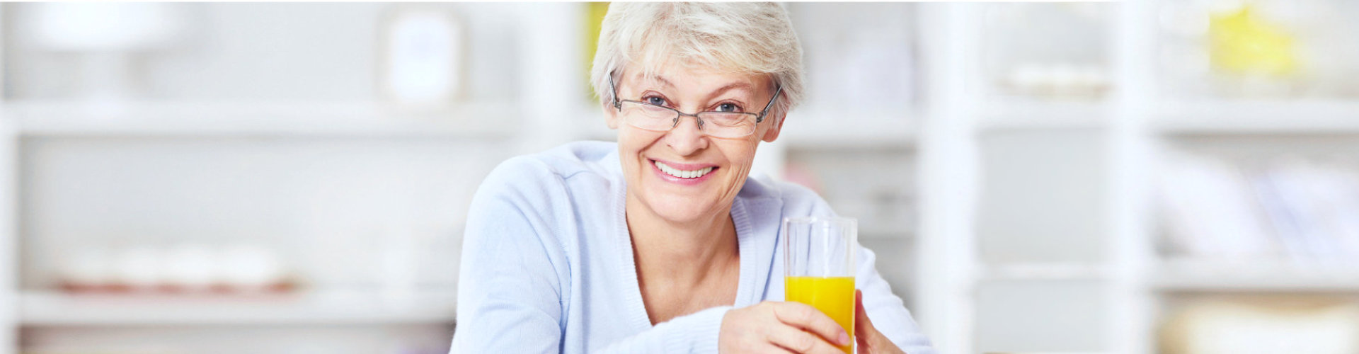 elder woman holding a glass of juice