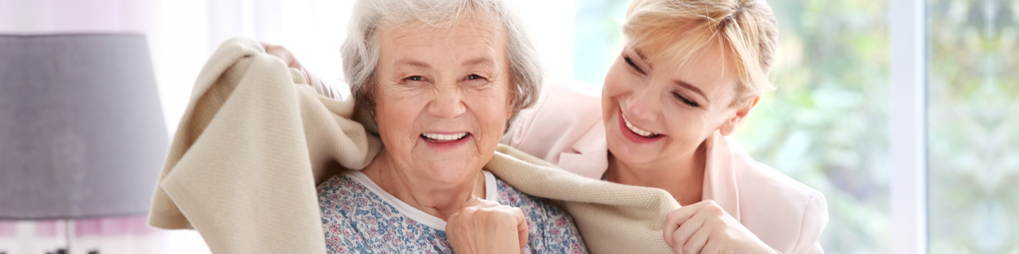 caregive giving blanket to her elderly