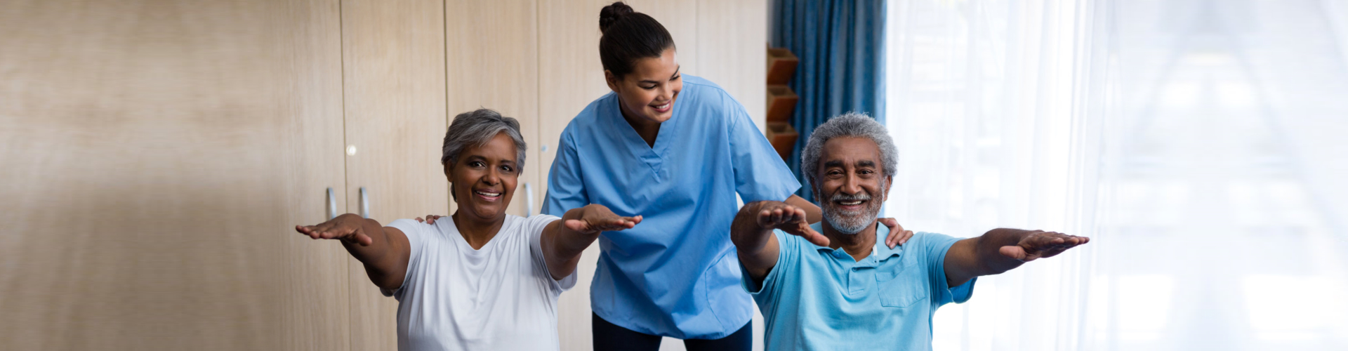 two seniors exercise with caregiver