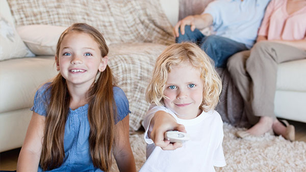 Two children watching tv with a remote control.