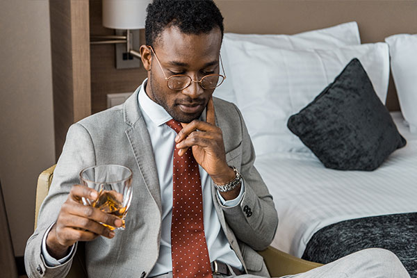 Man drinking in a hotel room