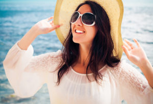Woman with hat, sunglasses, and shirt trying to minimize sun exposure