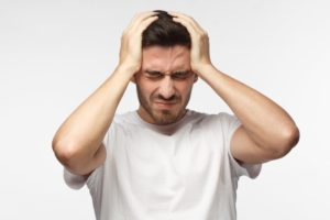 Man with a headache holding his head with both hands and a pained expression on his face