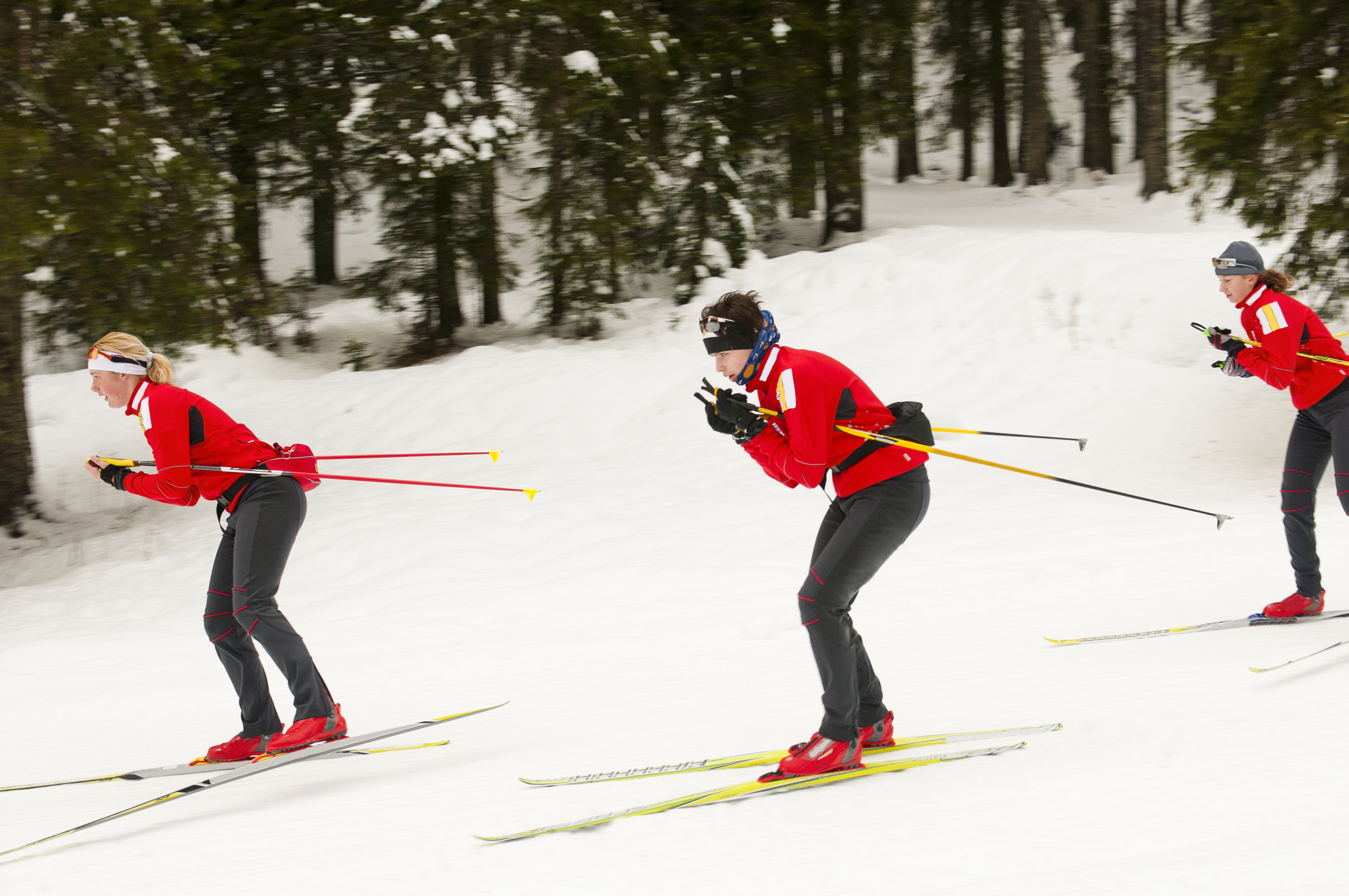 """Three young female cross country skiers at downhill, skating style"""