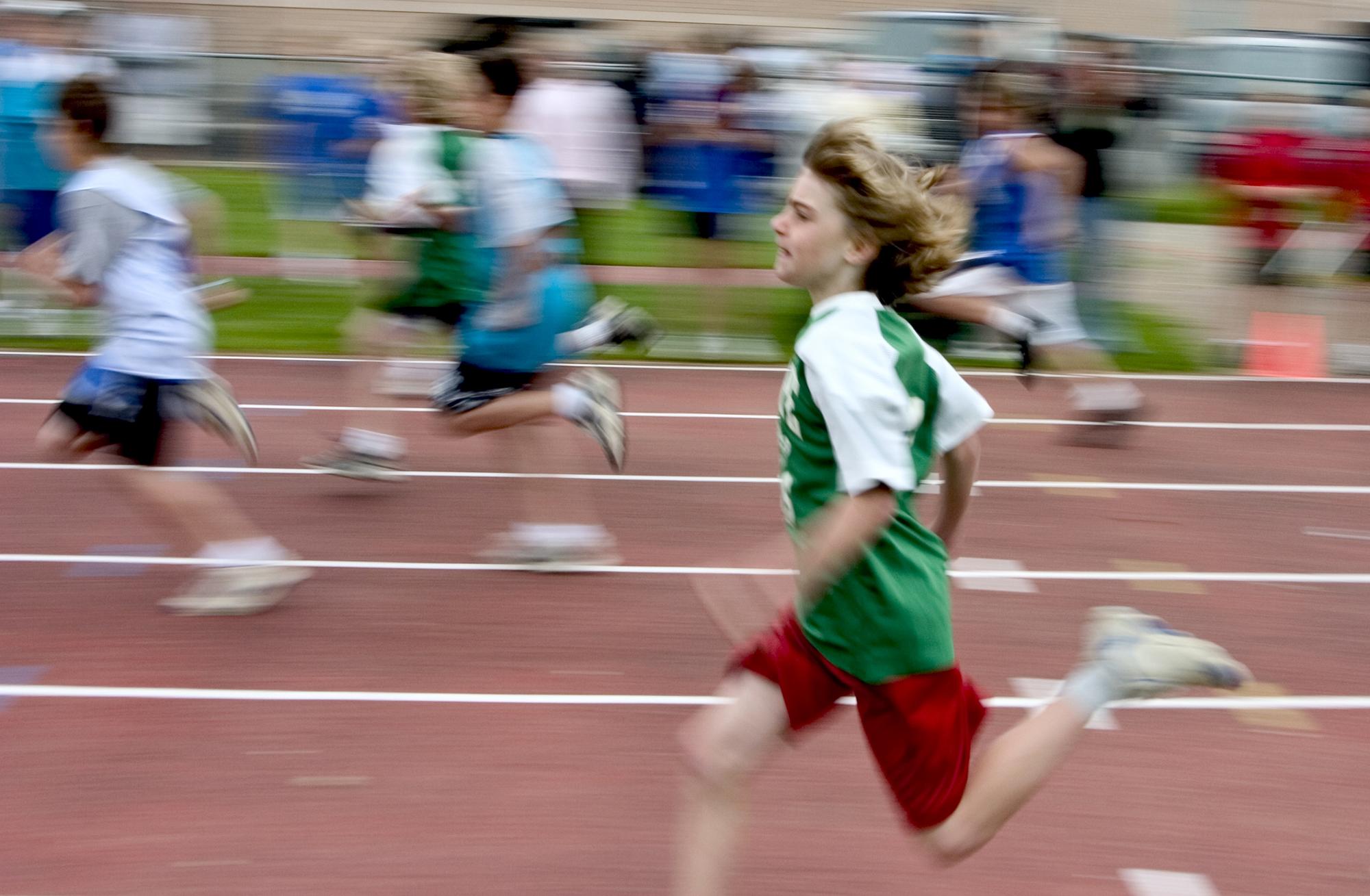 Boy running very fast in 100 meter foot race. Motion blur
