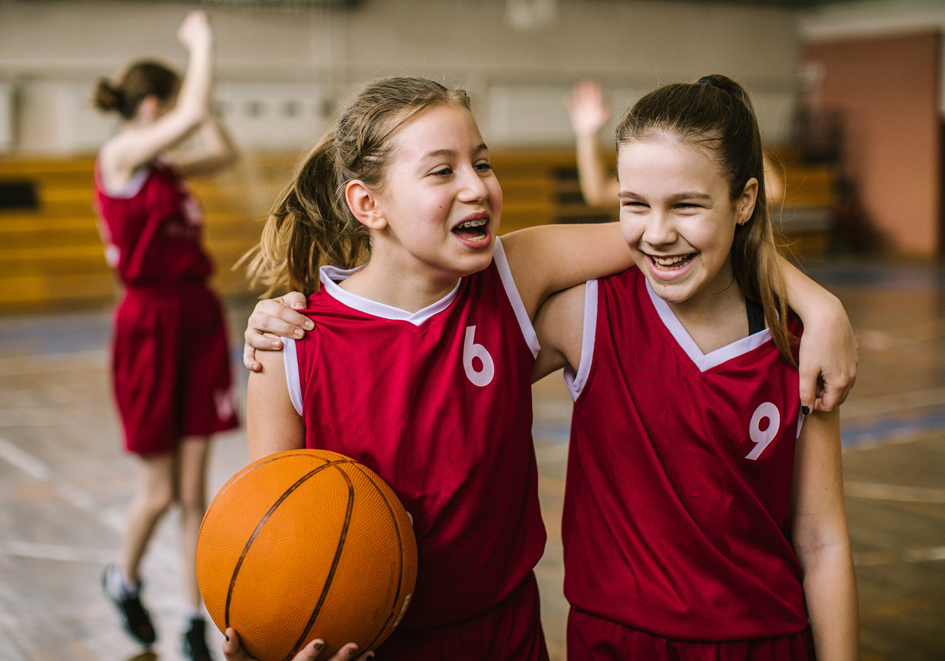 Cheerful teenage girls embracing after training, while walking and holding basketball ball, smiling lively indoor