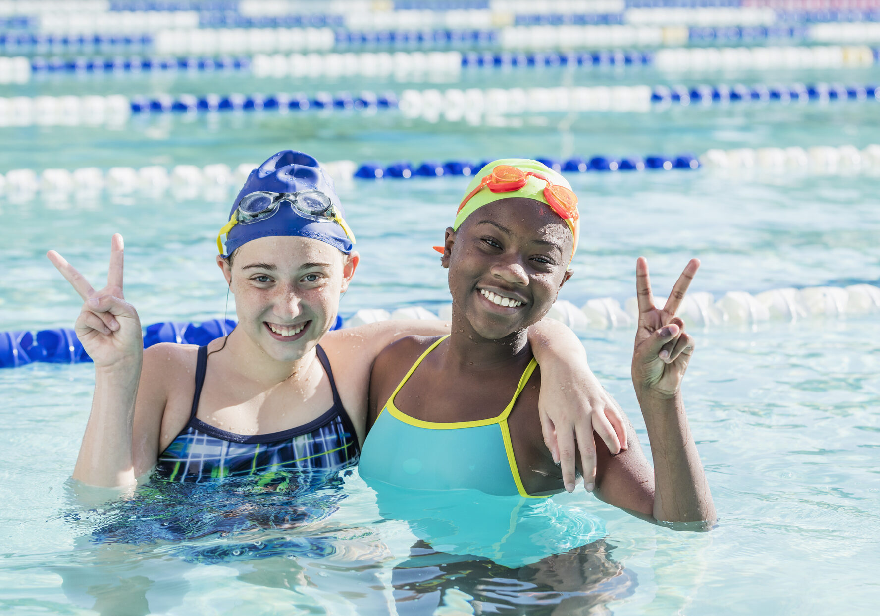 Two multi-ethnic girls standing together in a swimming pool, smiling at the camera. They are best friends having fun together on the swim team. They have swim caps and goggles on their heads. The African-American girl is 10 and her friend is 11 years old. They are holding their hands up in a peace sign, or v for victory.