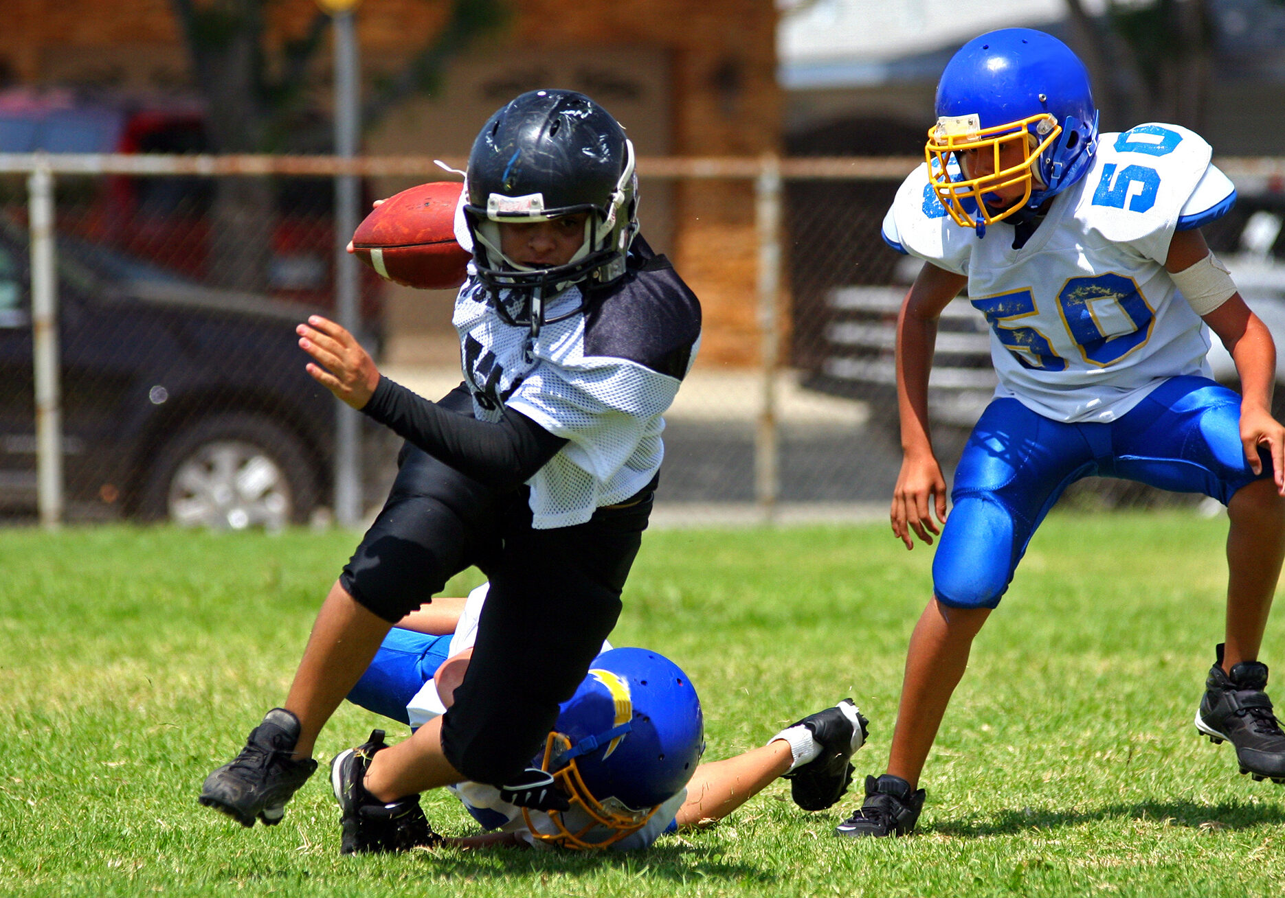 Young american football player running back breaking away from an attempted tackle. All logos and trademarks from uniforms, helmets and cleats have been removed in Photoshop