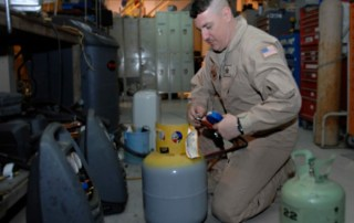 Man working with refrigerant, preparing for EPA substitute refrigerant revisions.