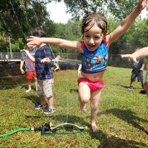 girl-jumping-over-sprinkler