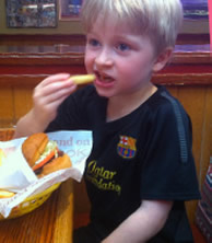 A young boy with severe allergies enjoys a cheeseburger. His server personally oversaw the cooking of the burger to ensure it was safe for him to eat.