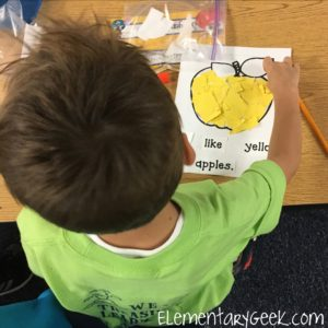 A student tearing his yellow construction paper to decorate his apple.