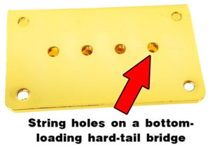 Bottom-loading hard-tail bridges have string holes in the base plate, as shown here. Strings are fed up through the body of the instrument. This gold 4-string hard-tail bridge is available from CBGitty.com.