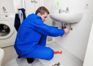 man in blue outfit under sink fixing pipe