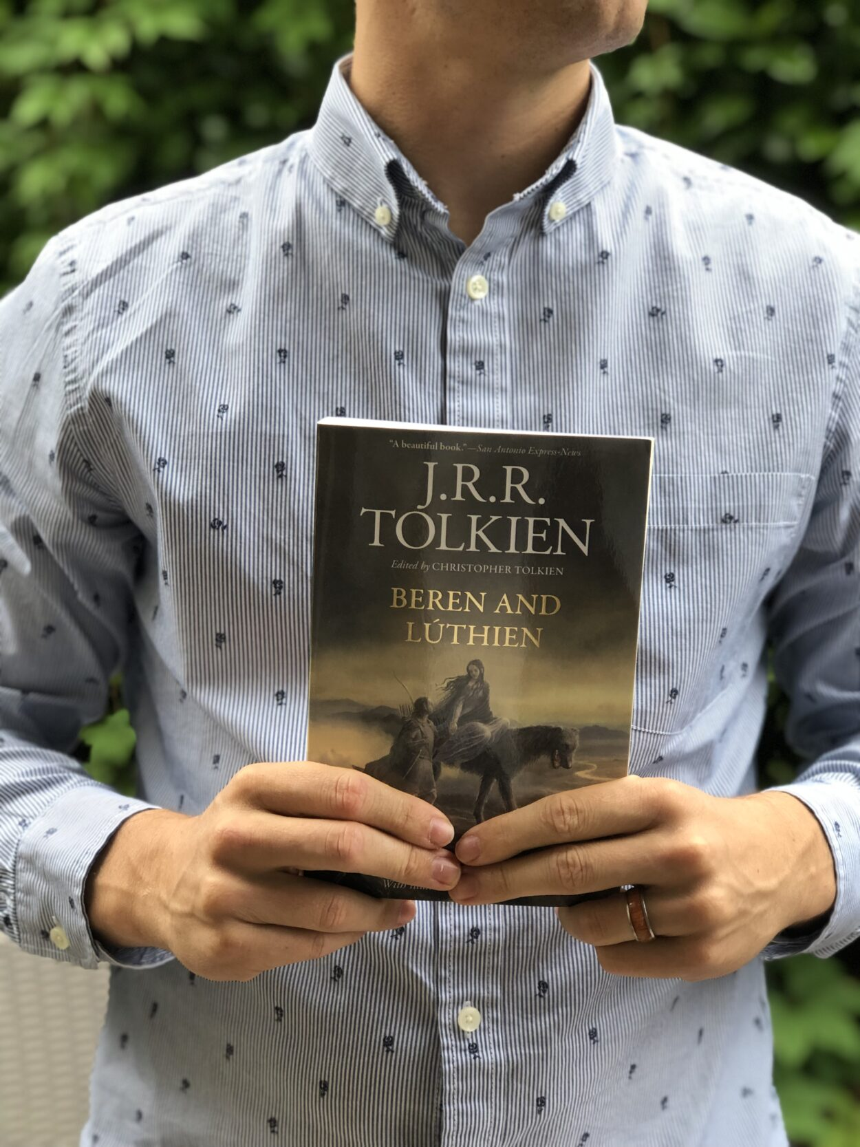 Man in dress shirt holding book by Tolkien