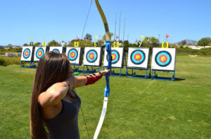 Female archer in field holding bow and arrow and getting ready to shoot target off in the distance