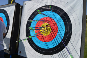 Archery target with arrows sticking into different parts of the target