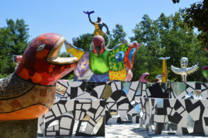 Entrance of Queen Calafia's Magical Cirlcle Garden featuring a wall with a vibrant red and orange snake and a black, white and mirrored tile mosaic maze
