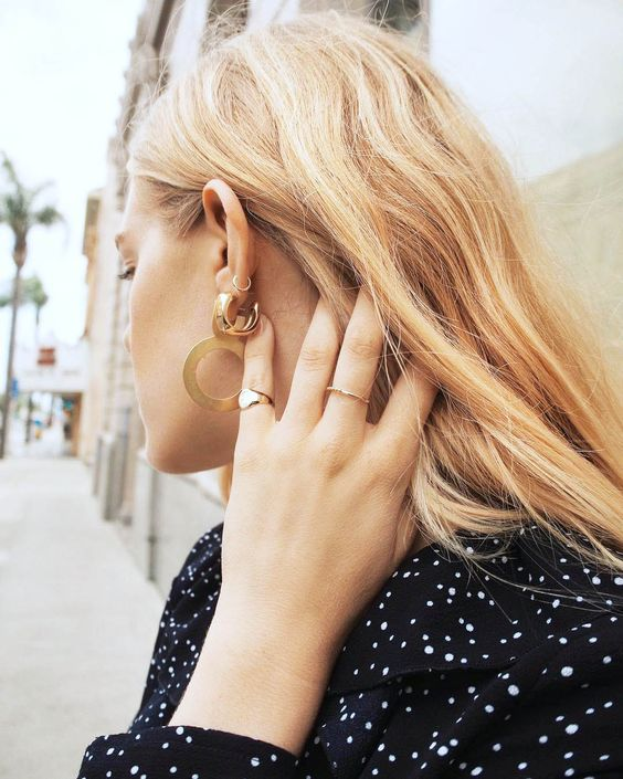 gold signet ring | woman moving hair away from face | Girlfriend Is Better