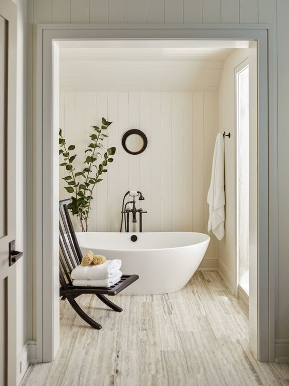 white interiors | pedestal bathtub natural wood flooring spa hygge bathroom | Girlfriend is Better