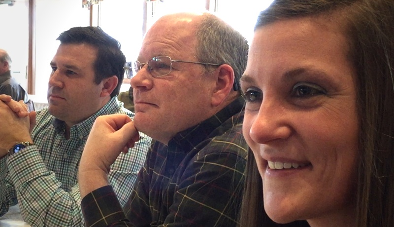 Two men and woman listening to Vicki Hitzges and smiling