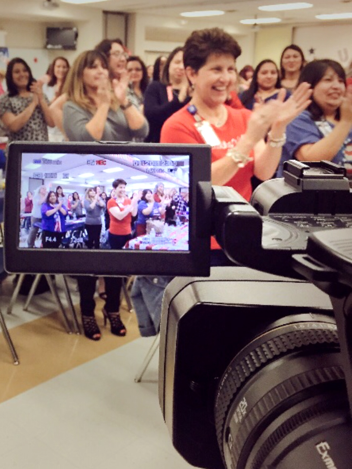 Large female audience standing and clapping with camera in foreground