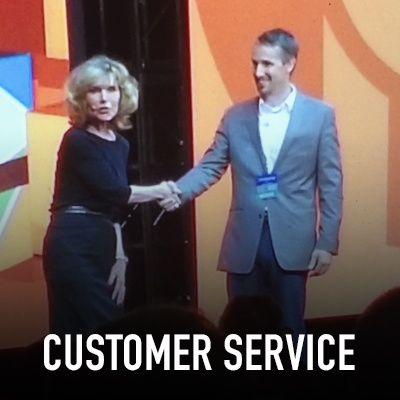 Vicki Hitzges on stage shaking hands with Customer Service title