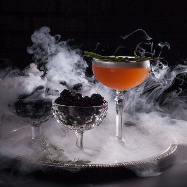 Orange cocktail for a Halloween shoot on a tray with two glasses filled with blackberries surrounded by smoke