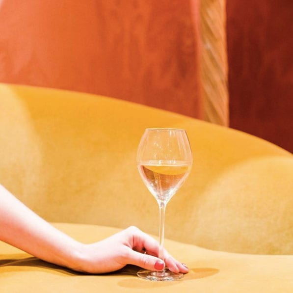A woman holding a glass filled with champagne on a yellow couch