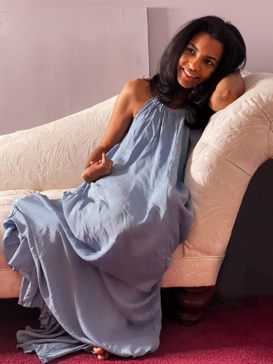 Brunette laying on a love site wearing a blue maxi dress and smiling while looking sideways and thinking of activities to do on Valentine's day.