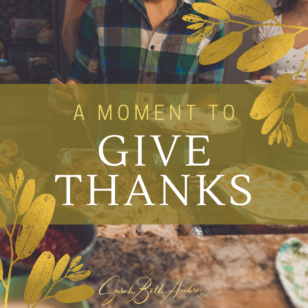 """A photo of a Thanksgiving dinner with turkey, stuffing, and pumpkin pie is the background. A young white woman is holding a serving fork over the turkey and in her other hand is a china plate. The words """"A Moment To Give Thanks"""" are over the photo in white. Decorative gold foil leaves are on the edges of the photo."""