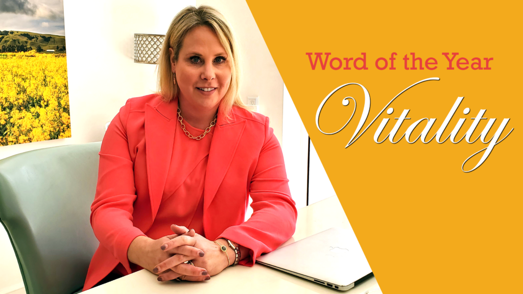 """A blonde woman in a coral-colored shirt and blazer looks at the camera. A white yellow triangle on the side of the image has the words """"word of the year"""" in matching pink and a cursive font in white reads """"vitality"""""""