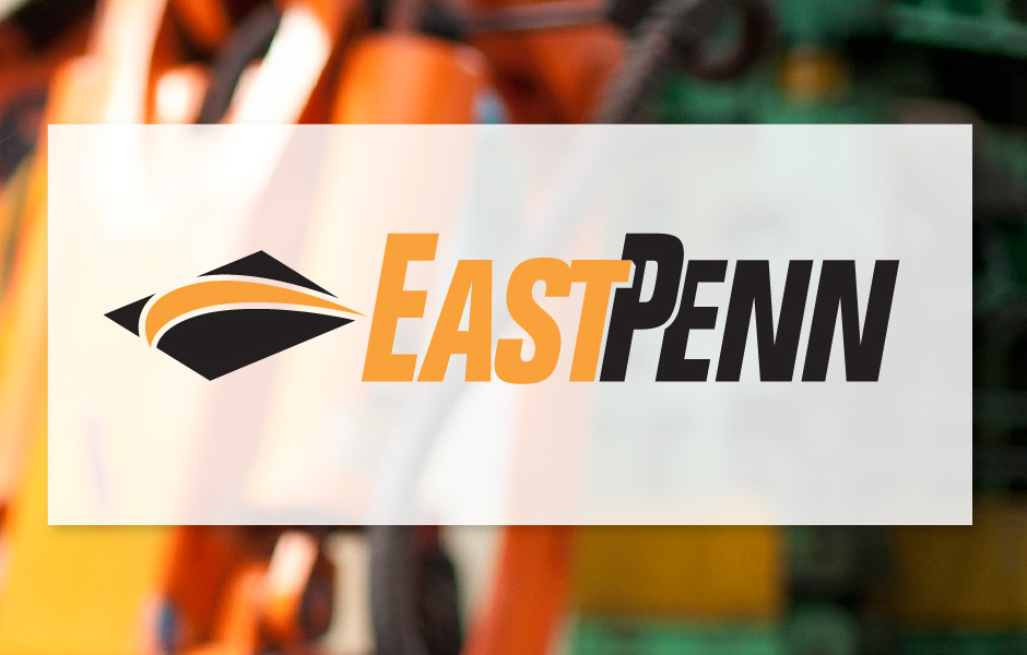 East Penn Logo, orange and black over manufacturing background