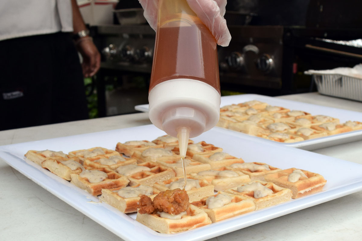 Spreading honey on southern chicken and waffler appetizers