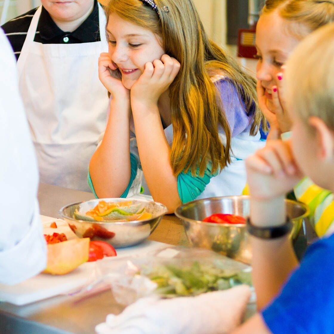 21331358 - kids learning how to cook in a cooking class.