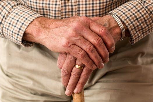 Old man's hands on cane elder abuse
