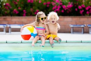 Boy and girl laughing by pool with beach ball Guardianship
