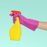 Person wearing a pink rubber glove holding a yellow squeeze bottle