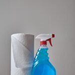 Squeeze bottle with blue liquid inside beside a roll of paper towels