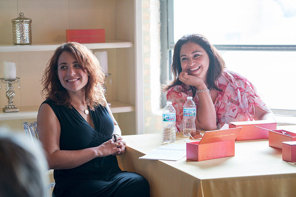 Two team members listening and enjoying a workshop at a table. They also have workbooks and materials at their place setting.