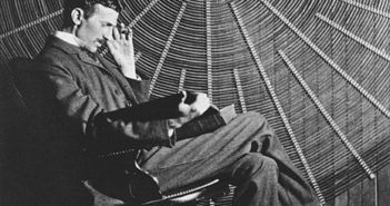 "Nikola Tesla, with Rudjer Boscovich's book ""Theoria Philosophiae Naturalis"", in front of the spiral coil of his high-voltage Tesla coil transformer at his East Houston St., New York, laboratory."