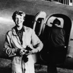 American aviator/pilot Amelia Earhart (1897-1937) standing by her Lockheed Electra dressed in overalls, with Fred Noonan getting into the plane in the background. Parnamerim airfield, Natal, Brazil.
