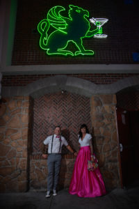Photographers of Las Vegas - Wedding Photography - wedding bride and groom standing stone arch and green neon sign