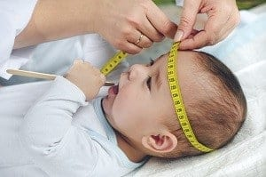 Pediatrician-measuring-babys-head