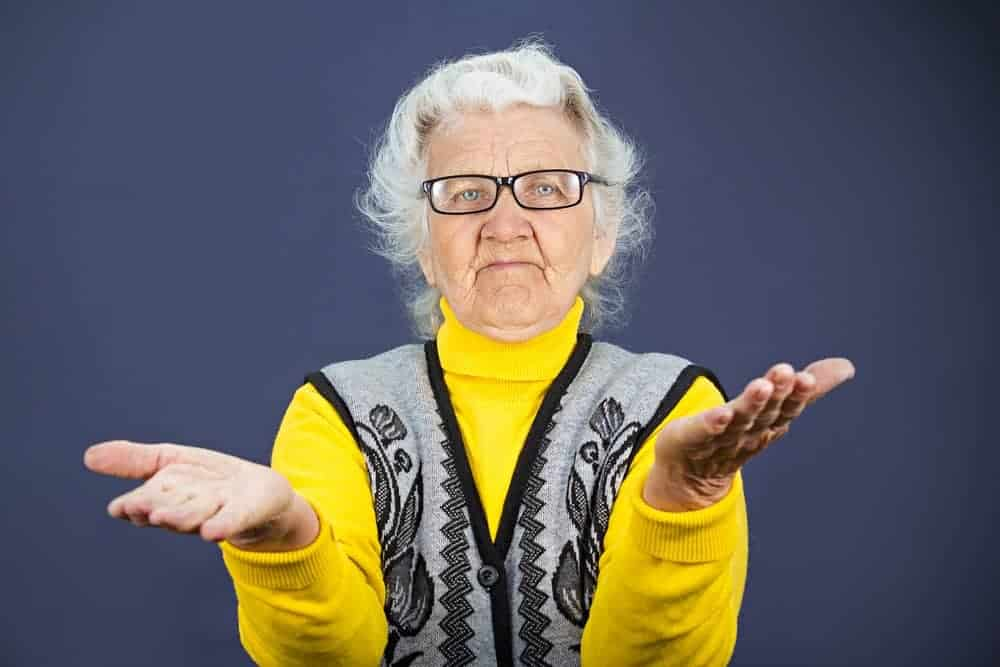 Closeup portrait, clueless senior, mature, elderly woman, arms out asking why whats problem who cares so what I don't know, isolated blue background. Negative human emotion, facial expression feeling