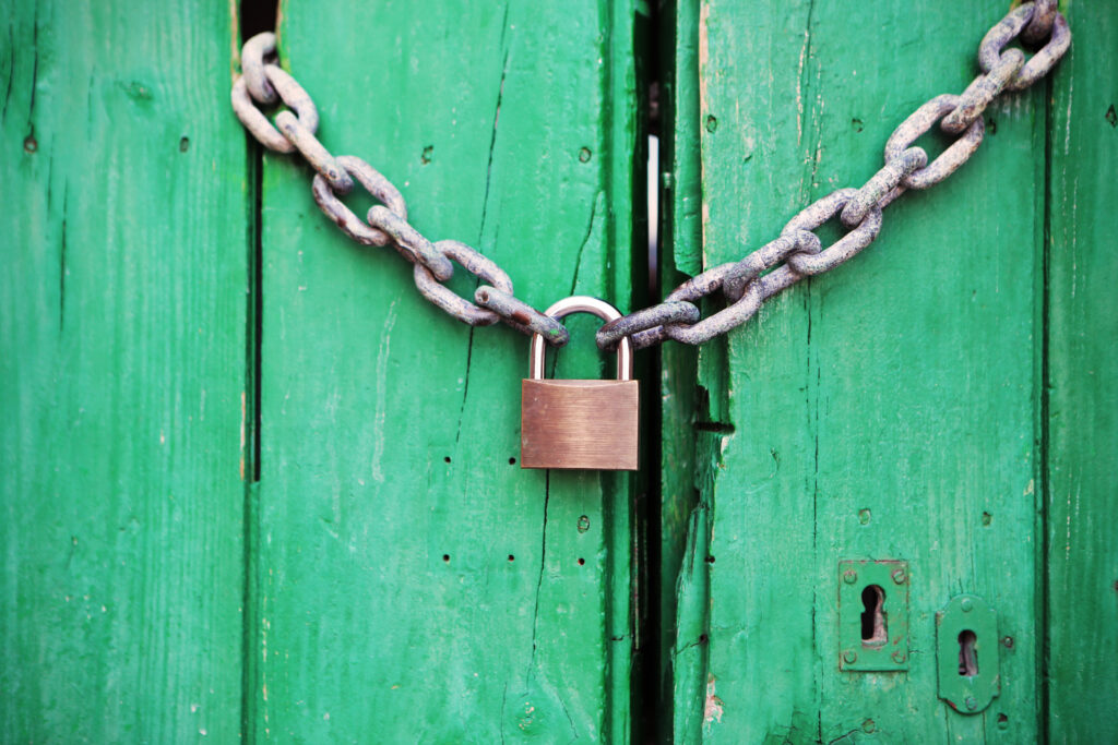 Green door with locked padlock