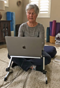 Joyce sitting cross-legged on cushion on floor while working on computer