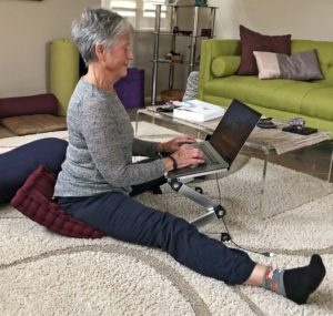 Joyce in wide v-sit on cushion on floor while working on computer