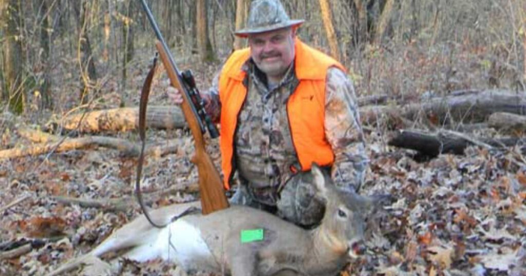 hunter with a gun and deer on ground